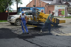 Laying of asphalt. The brigade of foreign workers, lay asphalt on the road Stock Photo