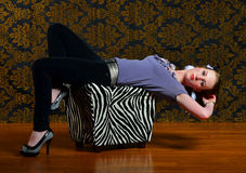 Laying back on a footstool. A beautiful woman lays back on a black and white Zebra patterned foot stool on wood laminated flooring and a patterned back ground Stock Photos