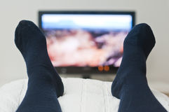 Laying in bed and watching tv Royalty Free Stock Images