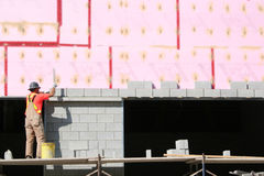 Laying Blocks. A laborer checks the row of blocks he has just laid.  The pink insulation has been blurred to avoid the trade names Royalty Free Stock Photo