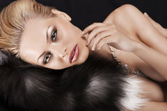 Laying blonde pretty girl on black fur Stock Photography