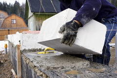 Laying bricks. Construction worker laying a huge block on foundation Royalty Free Stock Photos