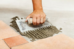 Laying ceramic floor tiles Stock Photo