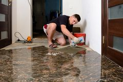Laying ceramic tiles while repairing in room and applying glue to the floor royalty free stock image