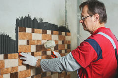 Laying Ceramic Tiles. Tiler knocking on the tiles with a rubber mallet royalty free stock photos