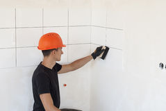 Laying ceramic tiles on a wall Royalty Free Stock Photo