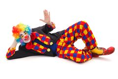 Laying clown. Clown laying on floor and waving with hand royalty free stock images
