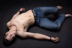 Laying down sportsman. Young sportsman lying down unconsciously on apparent asphalt floor Royalty Free Stock Photos