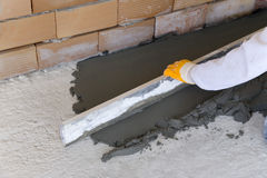 Laying of floor coating. Application of floor coating with a tool on the cement floor royalty free stock photos