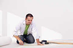 Laying flooring at home - the insulation layer. Man laying flooring at home - the isolation layer Royalty Free Stock Image