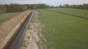Laying gas pipeline among green hills. Large high-pressure steel pipes prepared for immersion in the excavated trench. Land works. In the strategic industry stock video footage
