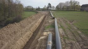 Laying gas pipeline among green hills. Large high-pressure steel pipes prepared for immersion in the excavated trench. Land works. In the strategic industry stock footage