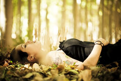 Laying girl on the forest. Young beautiful gothic girl laying over the foliage royalty free stock photos