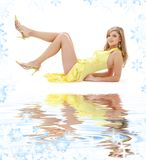 Laying girl in yellow dress on white sand Royalty Free Stock Photo