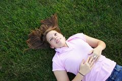 Laying in the grass. Young woman being silly laying in the grass Stock Photo