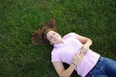 Laying in the grass. Young woman being silly laying in the grass Stock Photography
