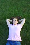 Laying in the grass. Young woman being silly laying in the grass Royalty Free Stock Photography