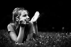 Laying on the grass. Girl laying in the grass relaxing after a hard day black & white Stock Images