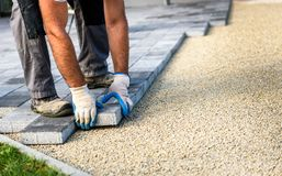 Laying gray concrete paving slabs in house courtyard driveway pa. Tio. Professional workers bricklayers are installing new tiles or slabs for driveway, sidewalk stock photos