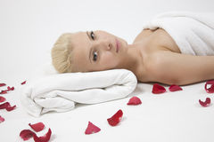Laying lady with rose petals. On isolated studio pictures Royalty Free Stock Photo