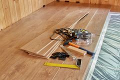Laying laminate covering on heat-insulated floor. Installation infrared carbon heating film for floor. Installing finished laminate floor  on a heat-insulated royalty free stock image