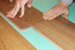 Laying laminate flooring. Worker installing new laminate flooring at home Royalty Free Stock Image