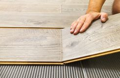 Laying laminate flooring in a flat. The hands of master closeup stock image