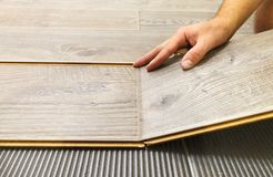 Laying laminate flooring in a flat. The hands of master closeup royalty free stock images