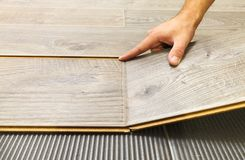 Laying laminate flooring in a flat. The hands of master closeup stock images
