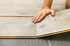 Laying laminate flooring in a flat. The hands of master closeup royalty free stock photography