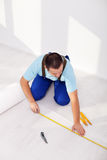 Laying laminate flooring at home. Measuring and cutting the isolation layer Stock Image