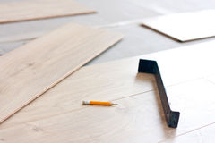 Laying laminate flooring. Tool for laying laminate flooring and laminate panels Stock Photos