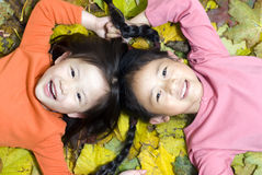 Laying in the leaves. Two sisters laying in a pile of autumn leaves Royalty Free Stock Photography