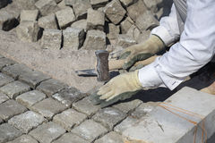 Laying natural granite stone cobbles in sand. Worker installing granite cubes for pathway. Laying natural granite stone cobbles in sand. Natural stone paving Royalty Free Stock Photos