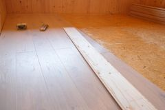 Laying of new parquet flooring in progress. Adhesive primer spread on old floor. Professional work, home improvement and renovation, carpentry and parquetry Royalty Free Stock Photos