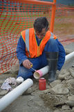 Laying new pipe. A plumber joins new pipes for a stormwater drain Royalty Free Stock Photos