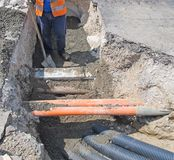 Laying of optical fiber and electric cables in a roadworks worke Stock Image
