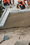 Laying paving bricks on soil Royalty Free Stock Photography