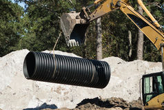 Laying Pipe. A backhoe carefully moves a pipe into place for a new water retention system Stock Image