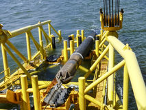 Laying of pipes with pipe-laying barge crane near the shore. Descent of the pipeline to a bottom exhausting with the pipelaying ba Royalty Free Stock Image