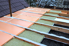 Laying slabs of heat insulation material between beams Stock Image