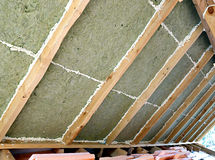 Laying slabs of heat insulation material. Between beams in the construction of roof in the frame house Stock Images