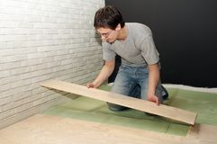 Laying work with laminated flooring. Young worker laying a floor with laminated flooring boards stock photo