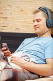 Laying young man listening music. This is a photograph of laying young man listening music royalty free stock photo