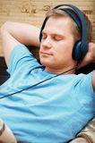 Laying young man listening music. This is a photograph of laying young man listening music stock photography