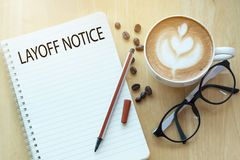 Layoff notice word on notebook with glasses, pencil and coffee cup on wooden table. Business concept stock photo