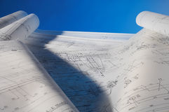Layout. Many different rolled-up engineering drawings on desk with blue background Stock Images
