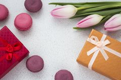 Layout of almond cookies with a bouquet of pink tulips and a gift in a box with a copy of space.  royalty free stock images