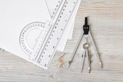 Layout with compass, protractor and centimeter ruler on wooden surface in top view. Workplace of draftsman, architect, constructor or designer. Engineering Stock Photo