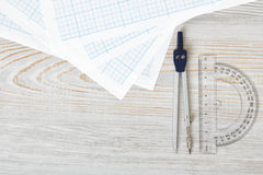 Layout with compass, protractor and graph paper on wooden surface in top view. Workplace of draftsman, architect, constructor or designer. Engineering work Stock Image